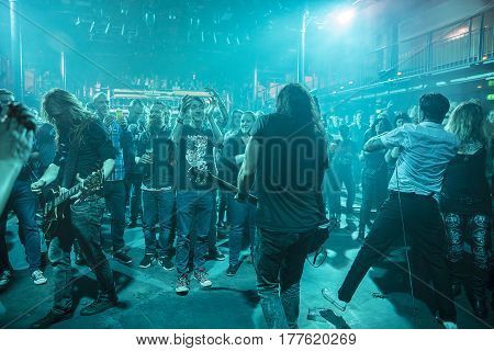 Amsterdam The Netherlands - March 19 2017: audience cheering while musicians of Norwegian hard rock band Audrey Horne plays in the crowd support act of Canadian hard rock heavy metal band Danko Jones at Melkweg