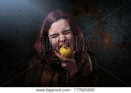 desperate woman is biting in an old apple