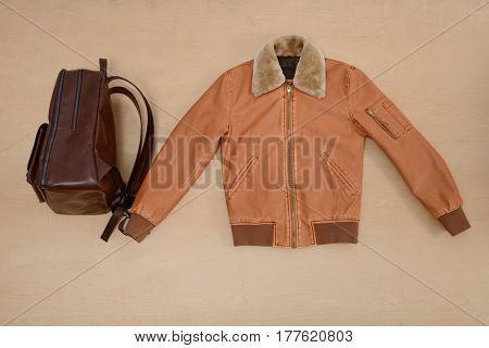 Handbag with jacket isolated on wooden background