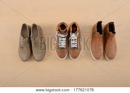 Fashion male three shoes on wooden background