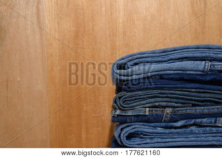 Jeans stacked on wooden background