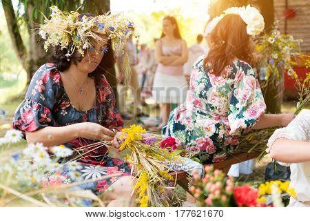 Minsk, Belarus - July 5, 2015: Woman Making Wreath Of Wild Flowers On Traditional Slavic Holiday Of
