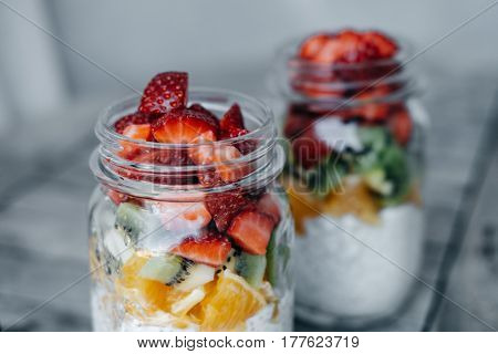 Closeup Glass Jar Of Healthy Breakfast With  Chia Pudding, Strawberry, Kiwi, Orange On Wooden Backgr