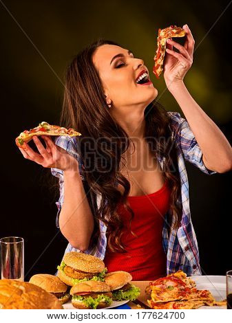 Woman eating pizza and hamburger. Student consume fast food. Girl opened her mouth to take bite of slice . Girl trying to eat a lot of junk. Advertise fast food on black background.