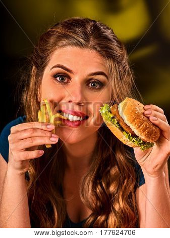 Woman eating french fries and hamburger. Student consume fast food. Girl bite of slice . Girl trying to eat a lot of junk. Advertise fast food on black background.