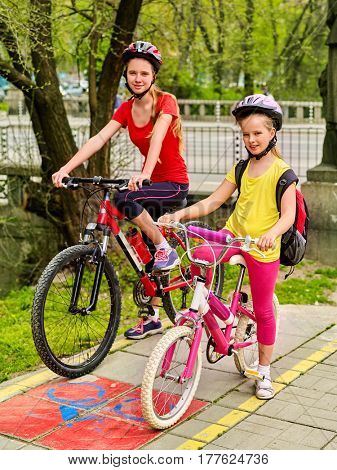 Family bike ride. Mother and daughter wearing bicycle helmet with rucksack . Children biking on yellow bike lane. Bike share program save money and time. Child in foreground teenager on background.