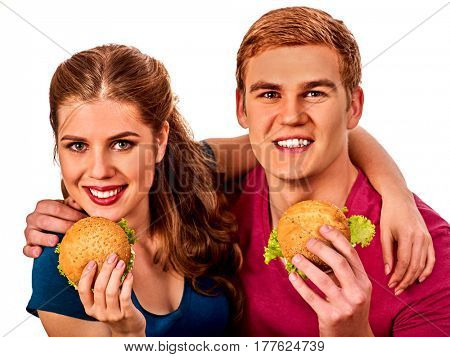 Couple eating fast food. Man and woman eat hamburger with ham . Friends holding two burder junk on white background isolated.
