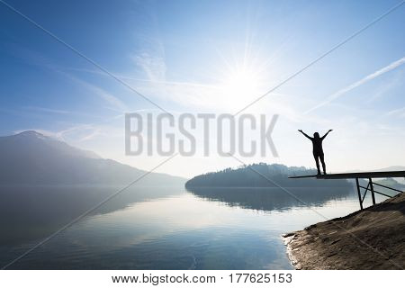 Landscape on the lake. Bright sun on a clear day. Figure of a woman with open arms.