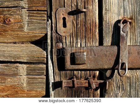 The old lock in textured wooden door