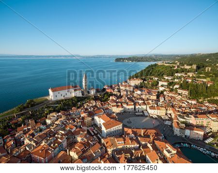 Old city Piran in Slovenia bird's eye view. Aerial photo with Tartini Square St. George's Parish Church old houses fortress and the sea. Sunset time.
