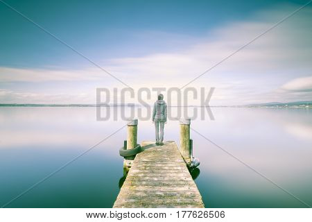 Double Exposure. Female figure on a wooden jetty. The shore of the lake a long exposure. Minimalism self reflex meditation.