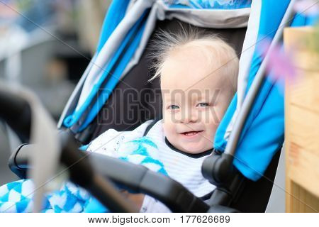 Baby boy with blue eyes sitting in modern stroller