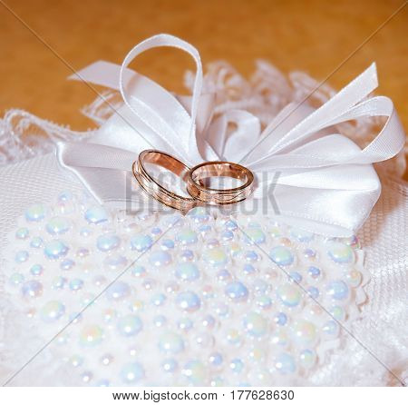 Gold wedding rings on the pincushion. Soft focus
