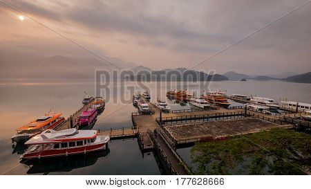 Long Exposure of harbor with boats in sun rise time in the morning at Sun Moon Lake Nantou city Taiwan