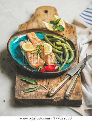 Oven roasted salmon fillet with lemon, rosemary, chilli pepper, poached green beans in blue ceramic plate on wooden board over grey marble background, selective focus. Dieting, clean eating concept