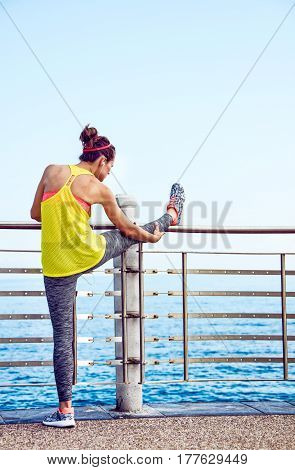 Young Athlete In Fitness Outfit Stretching At Embankment