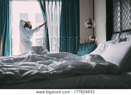Woman meets rainy morning in luxus hotel room