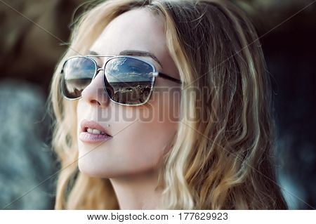 Macro portrait of woman face wearing sun glasses outdor with natural make up. Close up view of sunglasses with reflection of sea