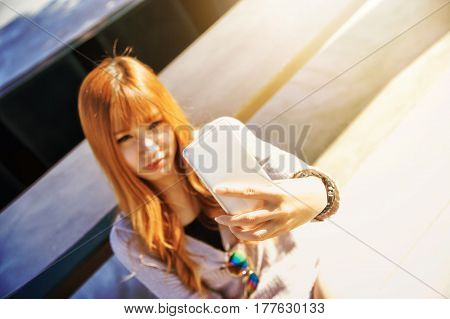 Asia Woman Sitting Against Bench And Selfie On Smart Phone