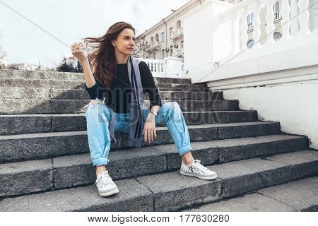 Fashion model wearing ripped boyfriend jeans and sneakers posing in the city street. Fashion urban outfit. Casual everyday clothing style.