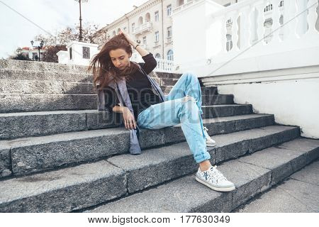 Fashion model wearing ripped boyfriend jeans and sneakers posing in the city street. Fashion urban outfit. Casual everyday clothing style. poster