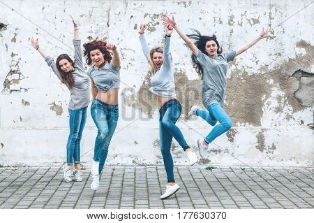 Group of four young diverse girls wearing blank gray tshirt and jeans posing against rough street wall, fashion urban clothing style, mockup for t-shirt print store