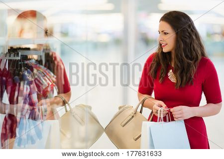 Shopaholic woman buying clothes in shopping mall