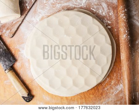 Step by step process of making home-made dumplings ravioli or pelmeni with minced meat filling using ravioli mold or ravioli maker. Ready for cooking raviolis on wooden board