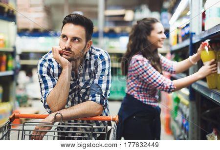 Husband bored while shopaholic woman enjoys shopping spree