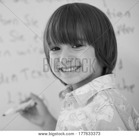 Cute little boy writing on white board