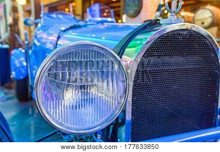 A Chrome Headlight on Classic Blue Roadster