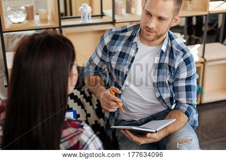 Ready to write. Intelligent delighted young man holding a pen and looking at his female colleague while being ready to take notes