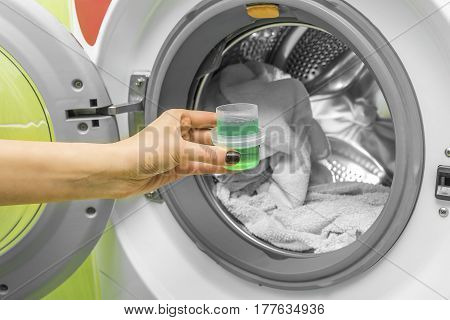 The hand pours liquid powder into the drum of the washing machine.