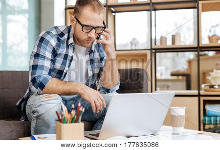 Distance communication. Serious handsome intelligent man sitting at the laptop and making a call while working in the office