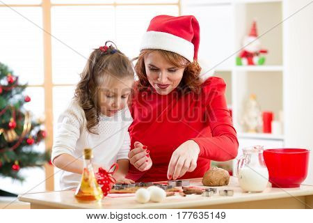Happy kid girl and her mother baking x-mas cookies together at festive decorated room