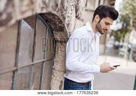 Handsome young man writing text message on mobilephone outdoors. Side view.