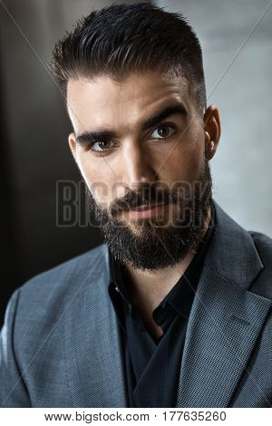 Portrait of bearded young businessman looking at camera.