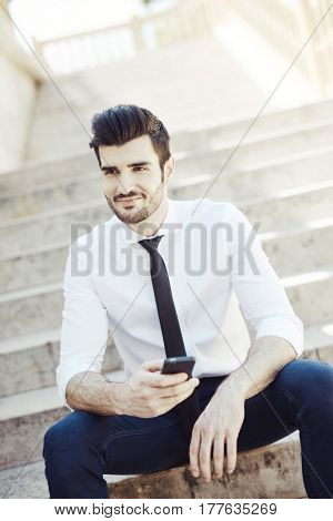 Outdoors portrait of handsome young man smiling using mobile.