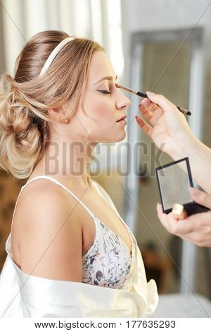 Makeup artist working on young bride. Side view.