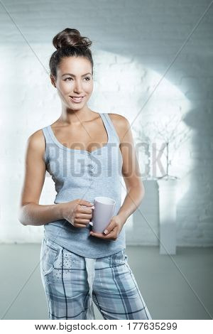 Morning photo of happy young woman in pajamas holding coffee.