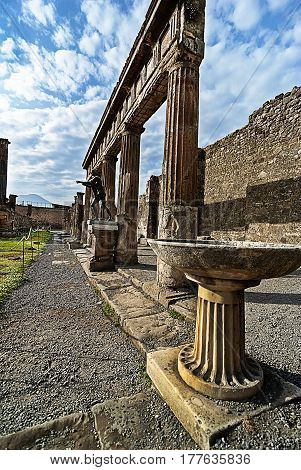 Pompeii is a ruined and partially buried Roman town-city near modern Naples in the Italian region of Campania, in the territory of the comune of Pompei. Along with Herculaneum, its sister city, Pompeii was destroyed, and completely buried, during a long c