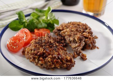 Schnitzel in walnuts and vegetables on a plate closeup