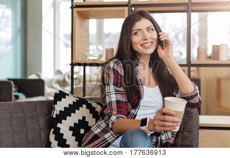 Wonderful wood. Happy nice brunette woman holding a cell phone and putting it to her ear while having a pleasant conversation with somebody