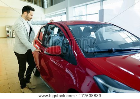 Handsome cute customer buying car at dealership