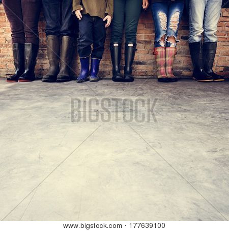 Group of people standing in a row with copy space on concrete floor