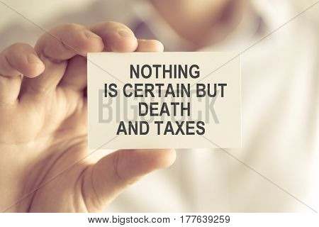 Businessman Holding Nothing Is Certain But Death And Taxes Message Card