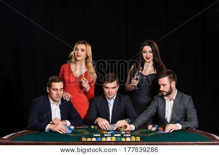 People at the poker table in casino. Men in suits, the women in beautiful dresses. Vacation with friends