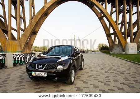 DNIPRO UKRAINE - APRIL 12 2016: NISSAN JUKE BROWN COLOR ON THE EMBANKMENT OF DNIPRO RIVER IN DNIPRO CITY UNDER THE BRIDGE SPRING TIME