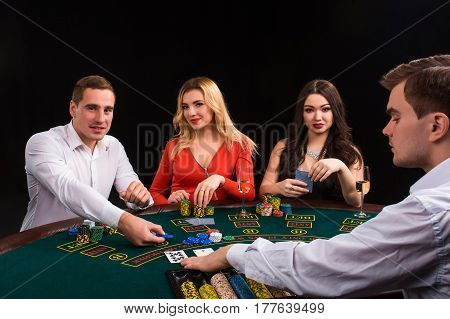 Happy people and dealer playing blackjack. Poker. Luxury women in dresses