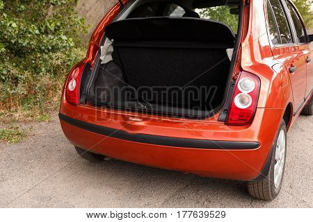 Car with open clean empty trunk of orange hatchback